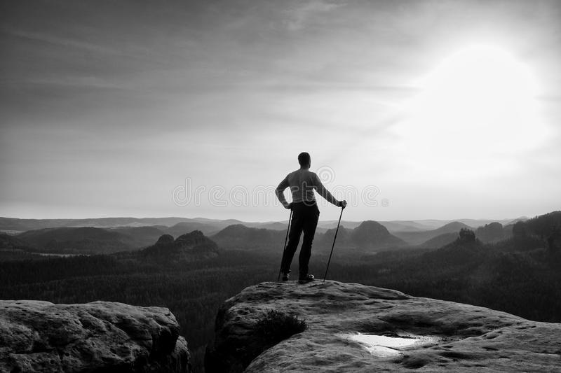 Ginger hair man in grey t-shirt and dark trekking trousers on sharp rock. Tourist with pole above misty valley. stock photo