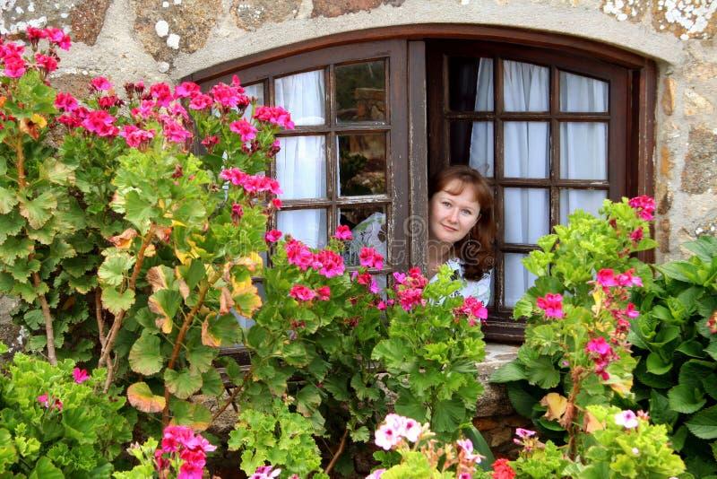 Ginger-haired Mädchen, das aus dem Fenster heraus schaut lizenzfreie stockfotografie