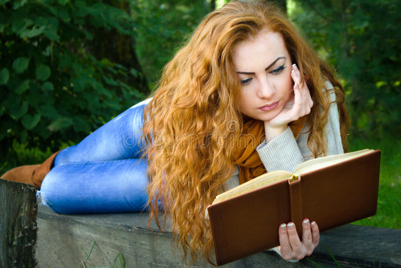 Ginger-haired woman reading a book in park lying on the bench stock photos