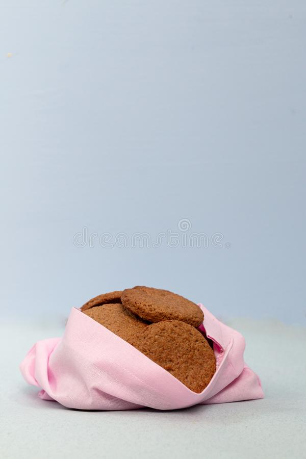Ginger homemade cookies in a handmade fabric pink bag  on a blue background. Ecology concept. Christmas card template. stock photography