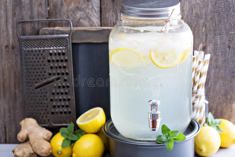 Ginger homemade lemonade in a beverage dispenser. Rustic lemonade stand with wooden and chalkboard background royalty free stock photo