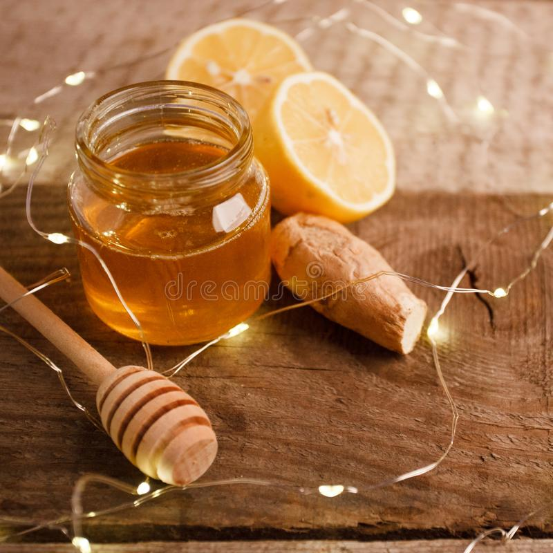 Ginger, honey and lemon, the concept of natural medicine, holiday garland, winter cozy home concept.  royalty free stock photo