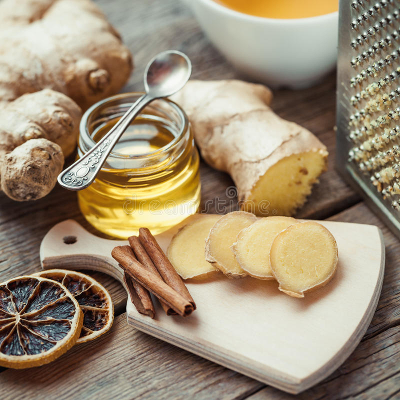 Ginger, jar of honey, dried lemon slice, cinnamon and grater stock images