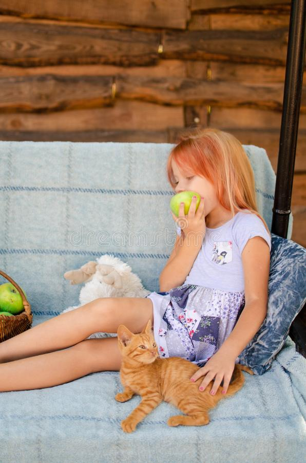 Ginger kitten lies near the girl on the garden swing. The girl strokes her pet. Little blonde caucasian girl with a red cat.  royalty free stock image