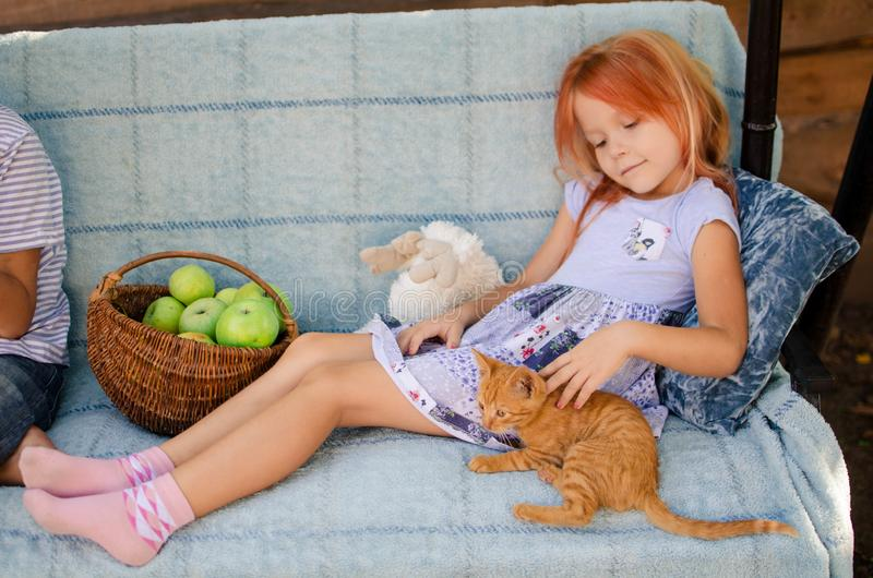 Ginger kitten lies near the girl on the garden swing. The girl strokes her pet. Little blonde caucasian girl with a red cat royalty free stock images