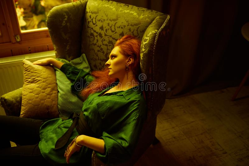 Vintage photo of Beautiful red haired young woman posing in old loft apartment in Tbilisi. Ginger lady posing in arm chair in loft apartment in Tbilisi. She stock photos