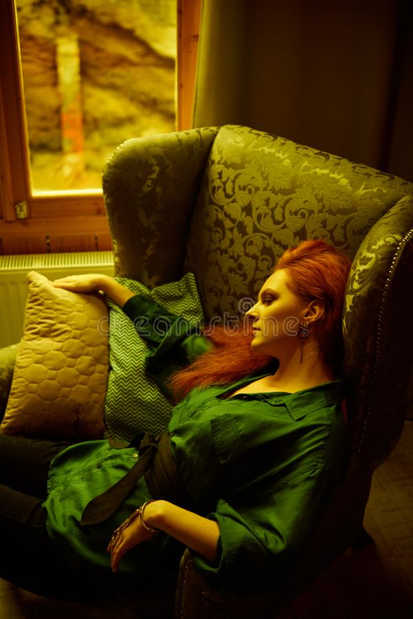 Vintage photo of Beautiful red haired young woman posing in old loft apartment in Tbilisi. Ginger lady posing in arm chair in loft apartment in Tbilisi. She royalty free stock image