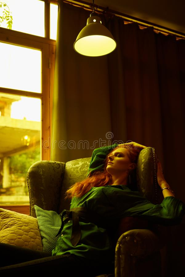 Vintage photo of Beautiful red haired young woman posing in old loft apartment in Tbilisi. Ginger lady posing in arm chair in loft apartment in Tbilisi. She royalty free stock photography