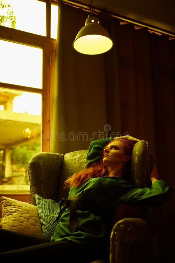 Vintage photo of Beautiful red haired young woman posing in old loft apartment in Tbilisi. Ginger lady posing in arm chair in loft apartment in Tbilisi. She royalty free stock images