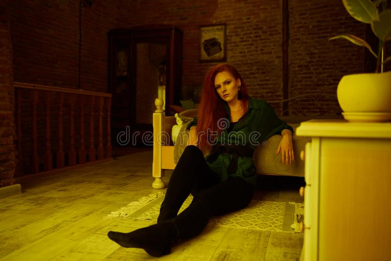 Vintage photo of Beautiful red haired young woman posing in old loft apartment in Tbilisi. Ginger lady posing in loft apartment in Tbilisi. She wears green shirt stock images