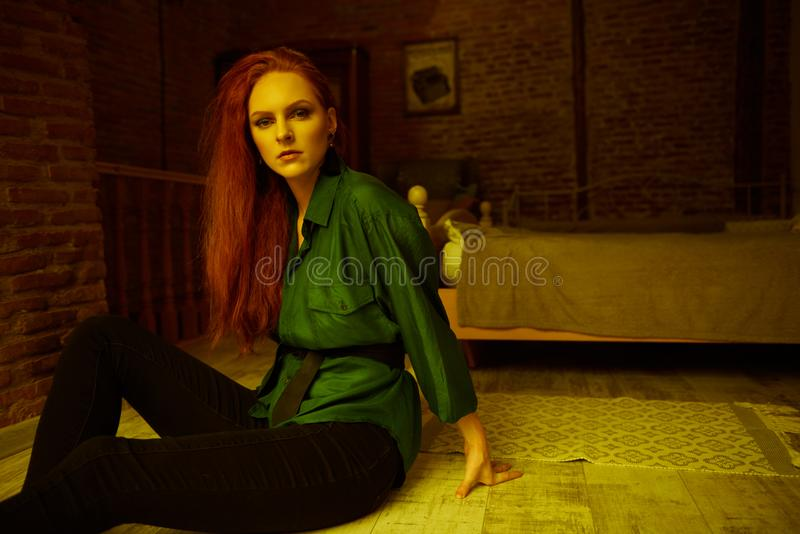 Vintage photo of Beautiful red haired young woman posing in old loft apartment in Tbilisi. Ginger lady posing in loft apartment in Tbilisi. She wears green shirt royalty free stock photography