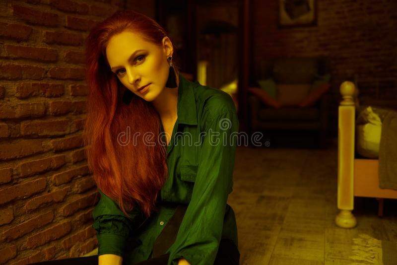Vintage photo of Beautiful red haired young woman posing in old loft apartment in Tbilisi. Ginger lady posing in loft apartment in Tbilisi. She wears green shirt royalty free stock images