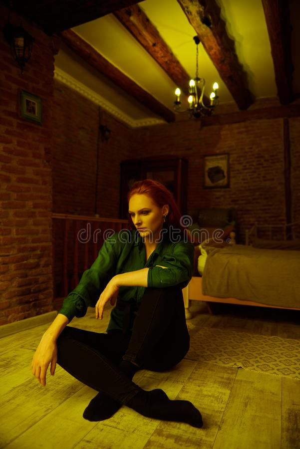 Vintage photo of Beautiful red haired young woman posing in old loft apartment in Tbilisi. Ginger lady posing in loft apartment in Tbilisi. She wears green shirt stock photography