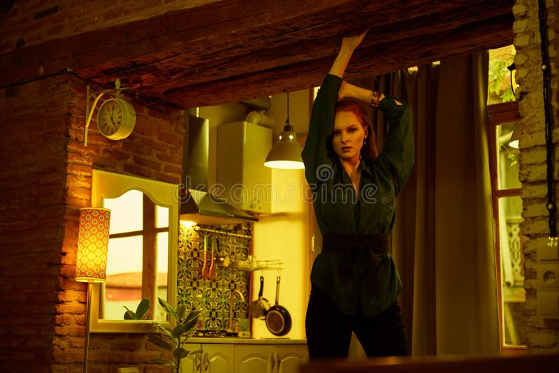 Vintage photo of Beautiful red haired young woman posing in old loft apartment in Tbilisi. Ginger lady posing in loft apartment in Tbilisii. She wears green stock images