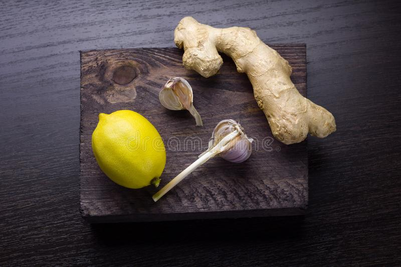 Ginger,lemon and garlic. Top view ginger,lemon and garlic on a wooden board royalty free stock photography