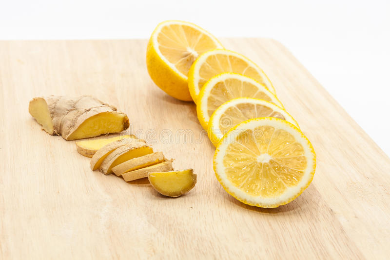 Ginger and lemon slices on wooden cutting board. Sliced ginger and lemon slices on wooden cutting board royalty free stock photos