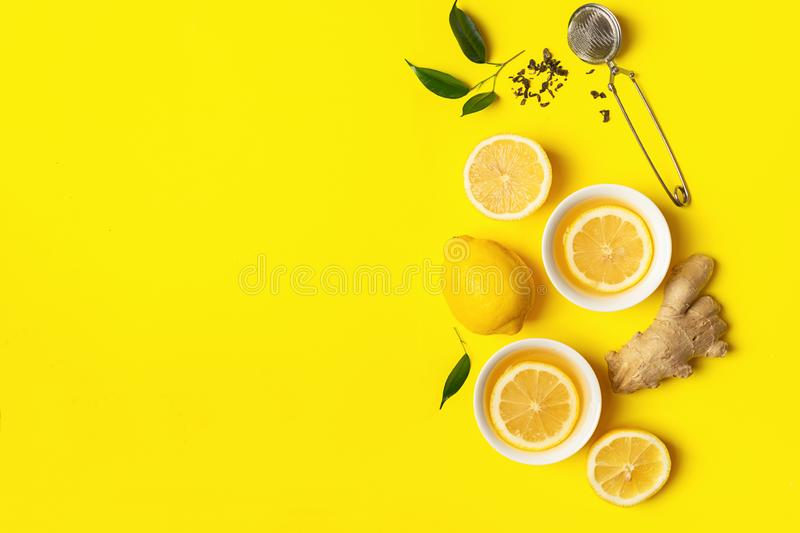 Ginger lemon tea or detox drink in a white cup on a bright yellow background. Healthy eating concept. Copy space. Horizontal frame. Top view flat layout royalty free stock photography