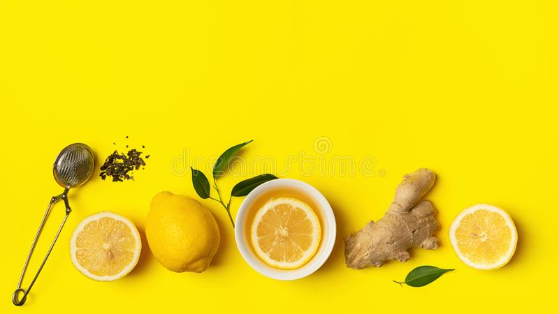 Ginger lemon tea or detox drink in a white cup on a bright yellow background. Healthy eating concept. Copy space. Horizontal frame. Top view flat layout stock photo