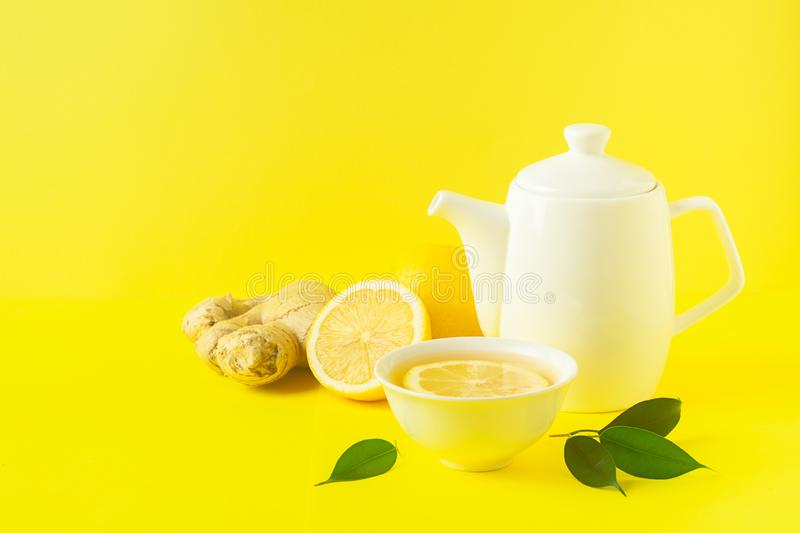 Ginger lemon tea or detox drink in a white cup and a teapot on a bright yellow background. Healthy eating concept. Horizontal frame. Copy space royalty free stock photography