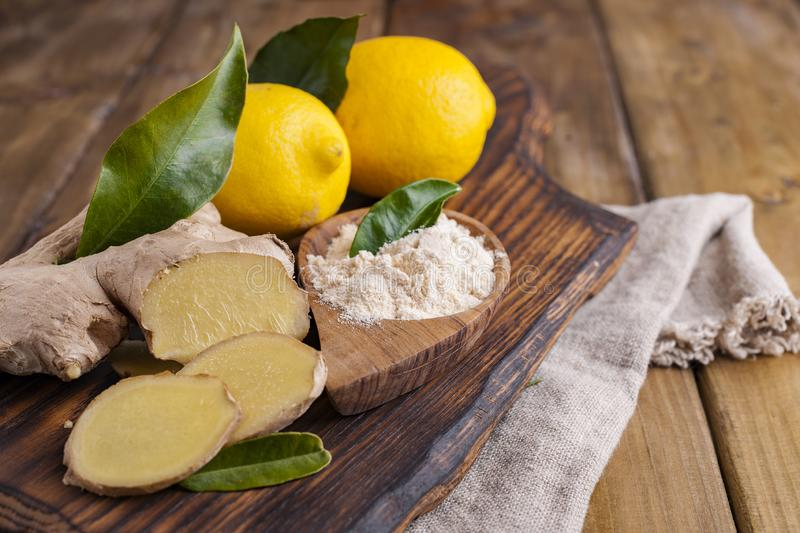 Ginger and lemon on a wooden background, Photo in a rustic style. Ingredients for warming and health drink. Alternative medicine. Free space for text stock photography