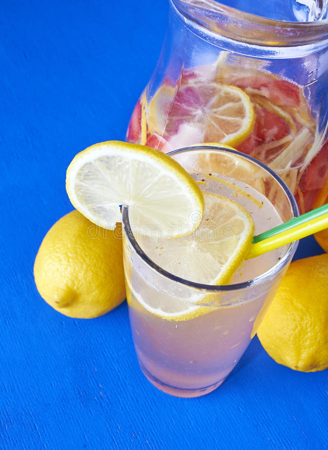 Ginger lemonade in glass with pithcer on back. Nice drink for realy hot summer stock photo