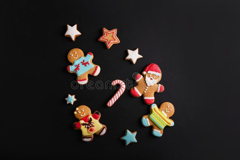 Ginger men with colored glaze on a black background . Gingerbread royalty free stock photos