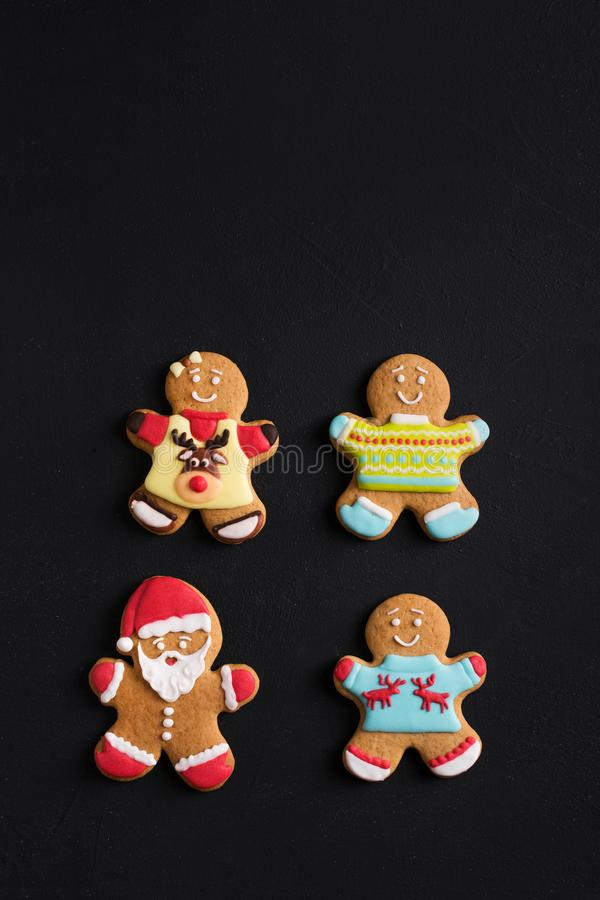 Ginger men with colored glaze on a black background . Gingerbread royalty free stock image