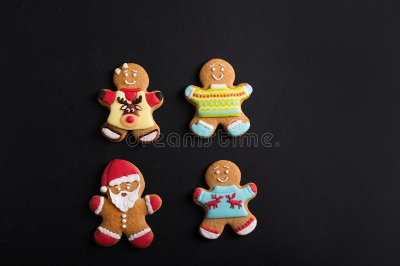 Ginger men with colored glaze on a black background . Gingerbread stock photo