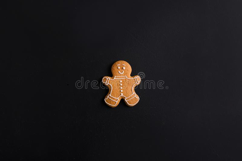Ginger men with colored glaze on a black background . Gingerbread stock images