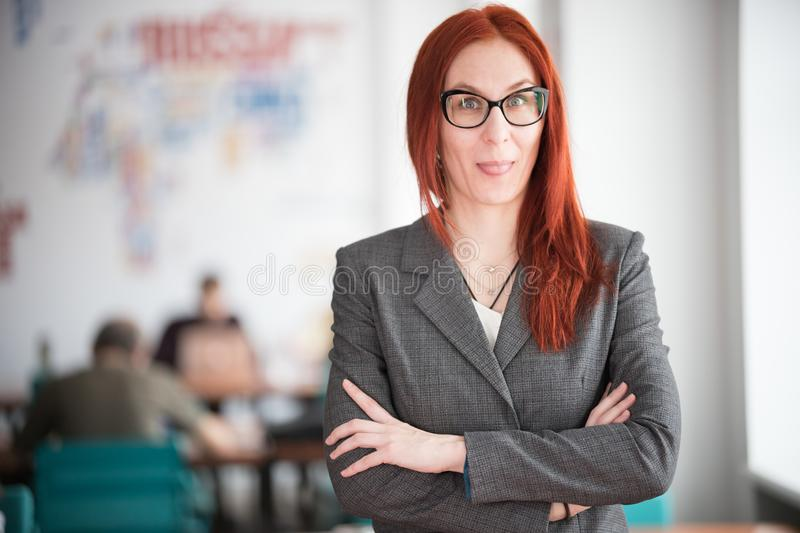 A ginger playful businesswoman in glasses standing at the office stock photography