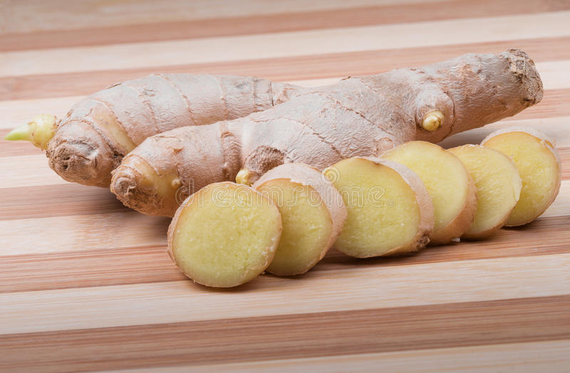 Ginger root on cutting board. Whole and sliced ginger root on wooden cutting board stock images