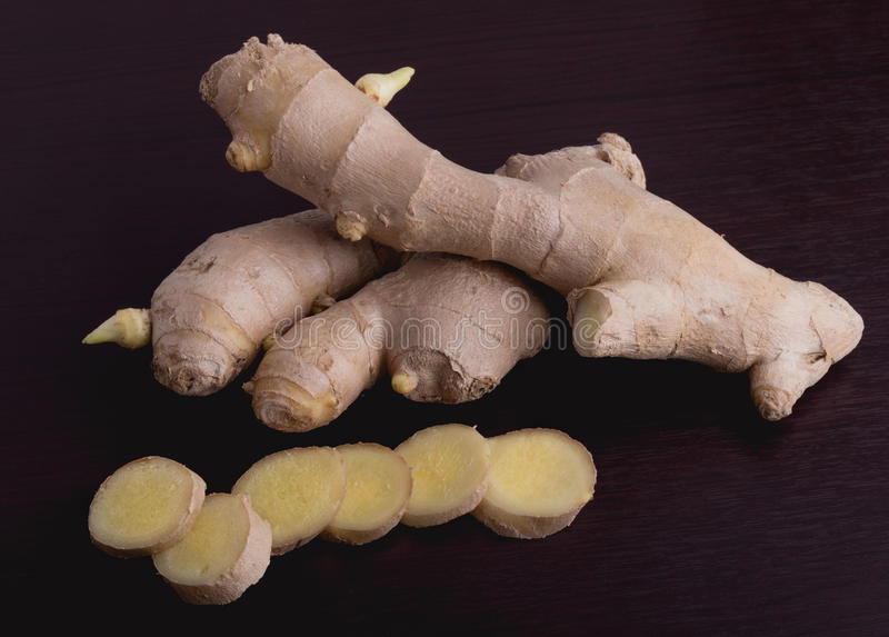 Ginger root on white background. Whole and sliced ginger root on wooden cutting board with a knife stock photo