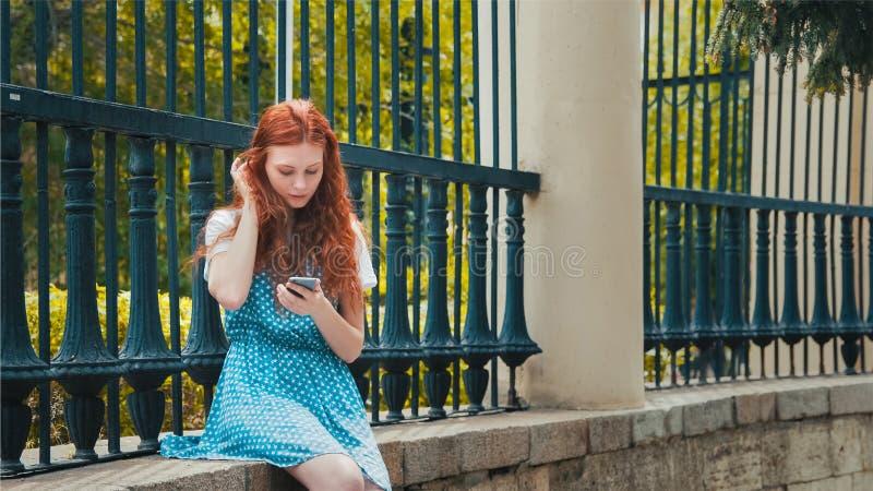 Ginger Rotkopfmädchen schaut ins Telefon stockfoto