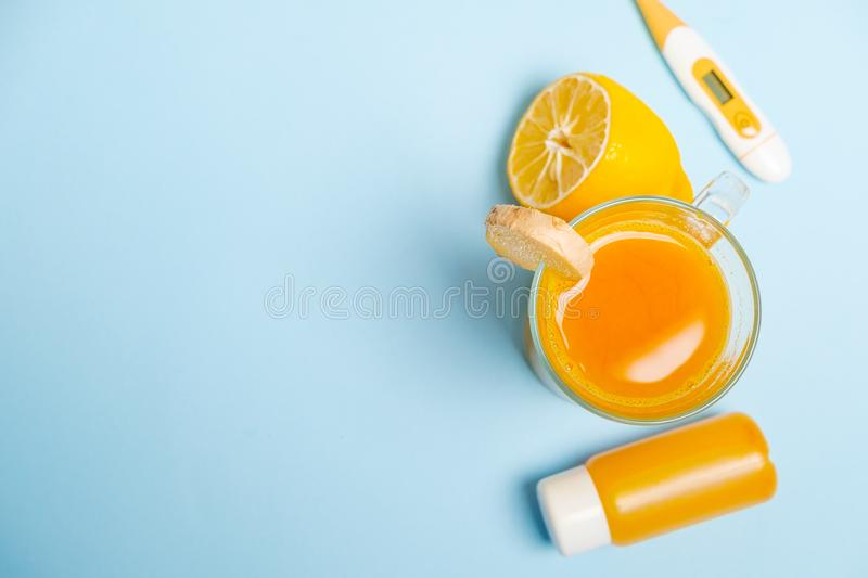 Ginger shot healthy drink with curd in a plastic bottle and thermometer on blue background. Immunity Boosting Tonic. Space for te royalty free stock image