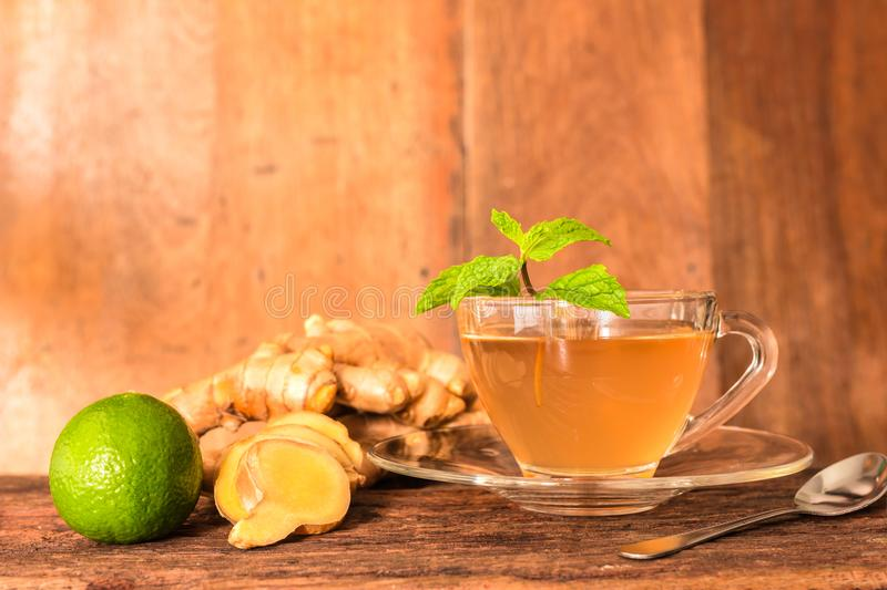 Ginger tea - Cup of ginger tea with green lemon royalty free stock images