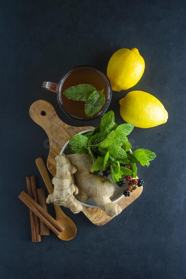 Ginger tea cup with lemons and mint leaves on dark background. Ginger tea, drink ingredients, cold and autumn time. Ginger tea cup with lemons and mint leaves on stock images