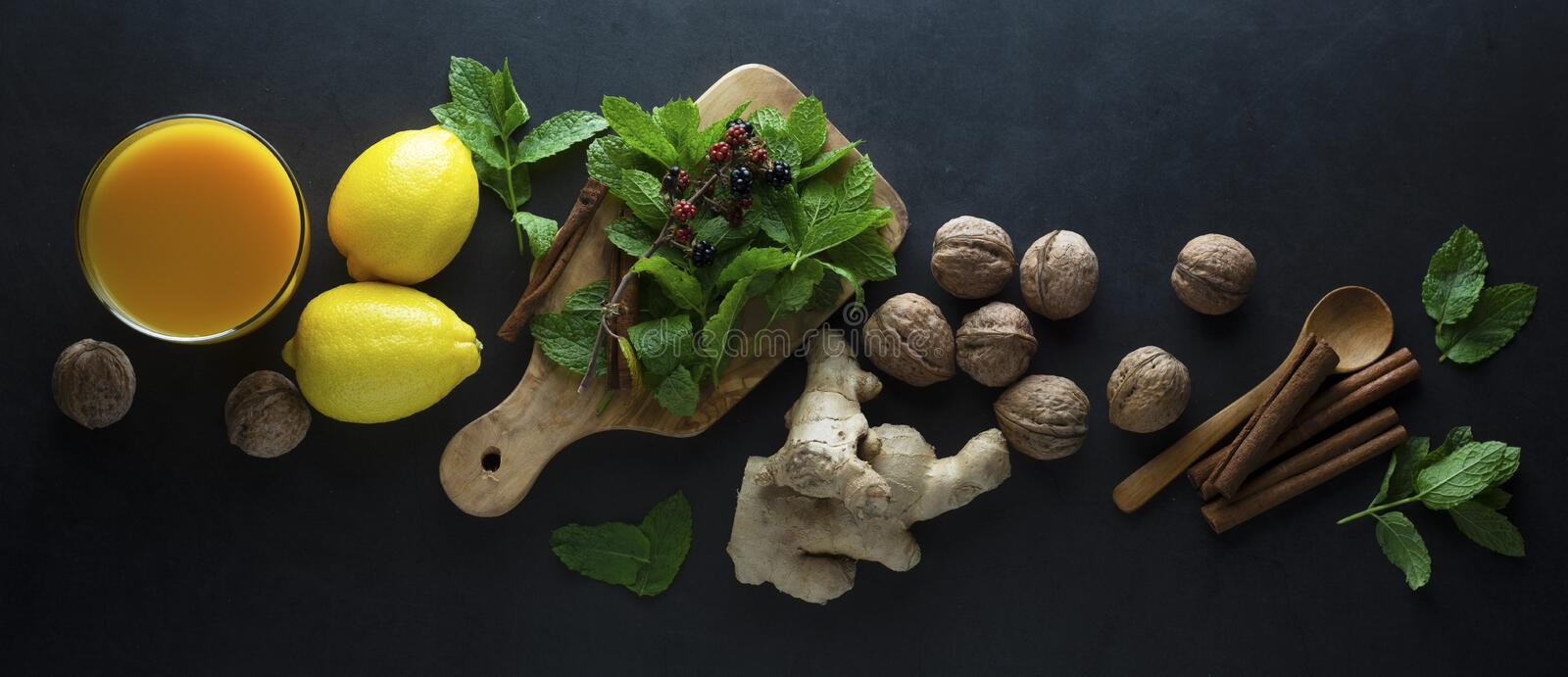 Ginger tea cup with lemons and mint leaves on dark background. Ginger tea, drink ingredients, cold and autumn time. Banner. Ginger tea cup with lemons and mint stock photography