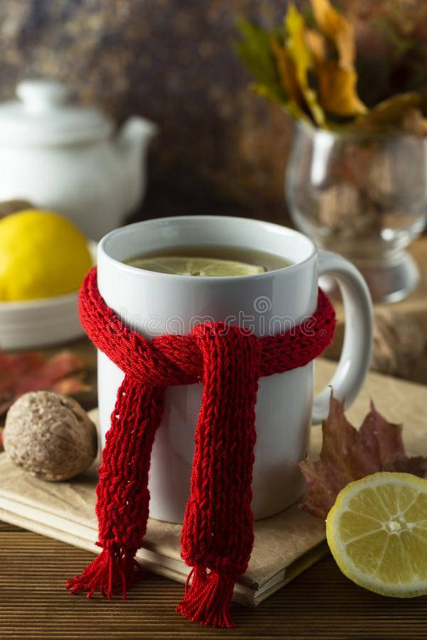 Ginger tea with honey and lemon. Tea cup with knitted red scarf. Autumn or winter warm drink. Wooden background royalty free stock image