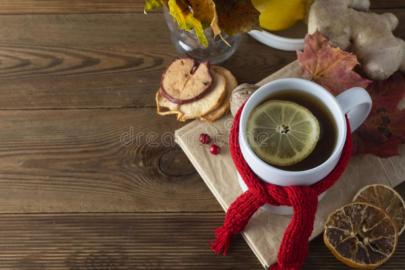 Ginger tea with honey and lemon. Tea cup with knitted red scarf. Autumn or winter warm drink. Wooden background stock images
