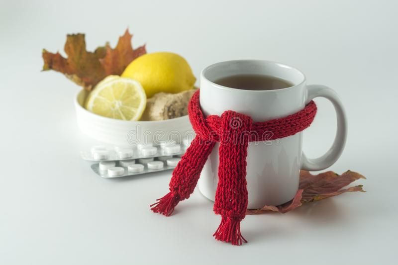Ginger tea with honey and lemon. Tea cup with knitted red scarf. Autumn or winter warm drink. White background stock photos