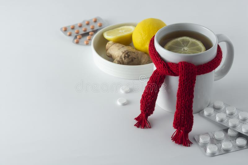 Ginger tea with honey and lemon. Tea cup with knitted red scarf. Autumn or winter warm drink. White background royalty free stock photography