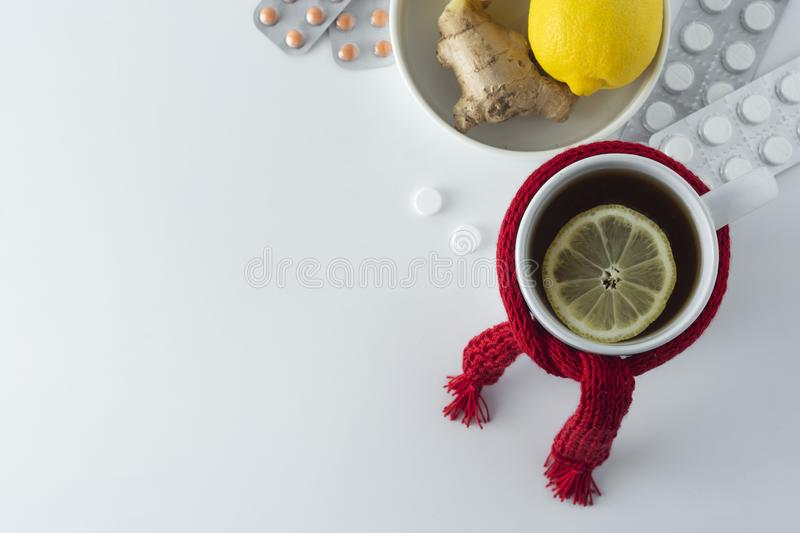 Ginger tea with honey and lemon. Tea cup with knitted red scarf. Autumn or winter warm drink. White background royalty free stock photos