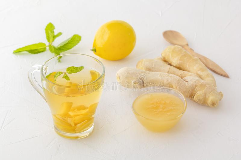 Ginger tea with lemon, honey and mint on a white wooden table royalty free stock photo