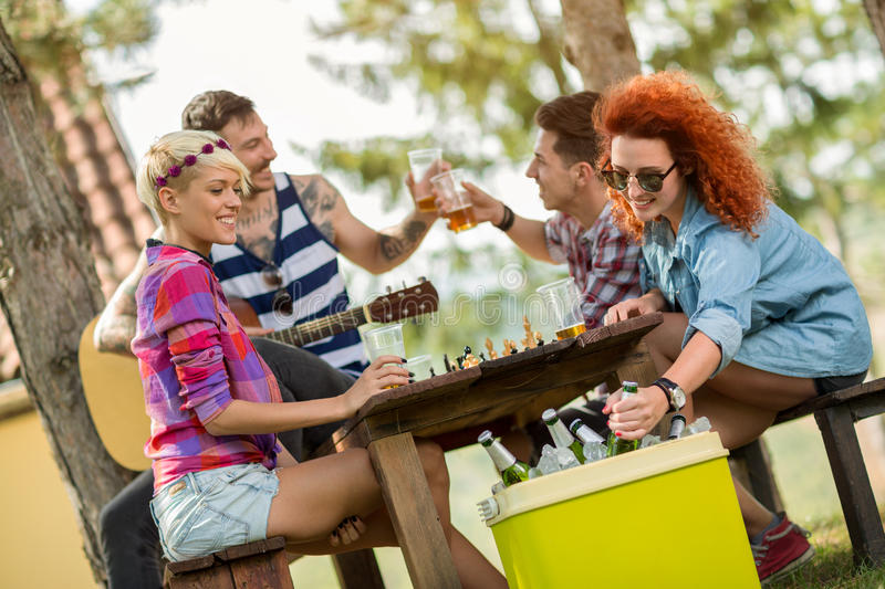 Ginger woman takes out cold beer from handheld refrigerator. Ginger women takes out cold beer from green picnic handheld refrigerator royalty free stock images