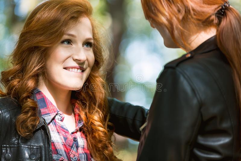 Woman biting her lip. Ginger women biting her lip while looking at other girl royalty free stock images