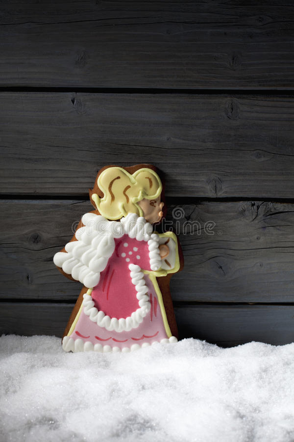 Gingerbread christmas angel on heap of snow against wooden background royalty free stock photos