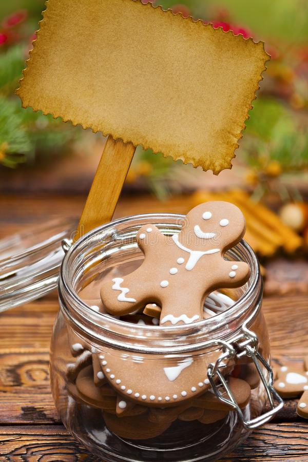 Gingerbread Christmas cookies in a jar and blank paper sheet on wooden table stock images