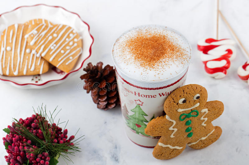 Gingerbread cookie man and hot cup of cappuccino. Traditional Christmas dessert. Copy space.  royalty free stock photo