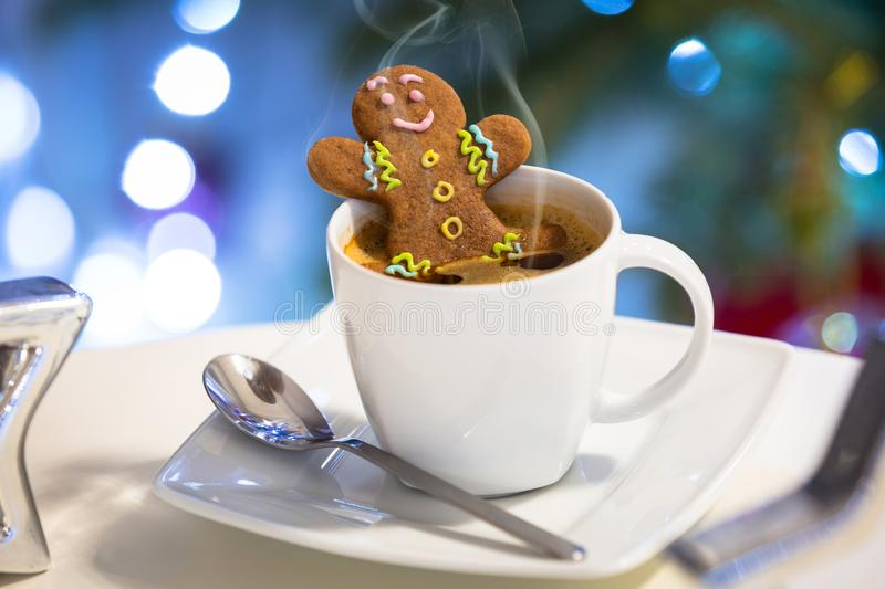 Gingerbread cookie man takes a bath in the cup of hot coffee with christmas background royalty free stock images