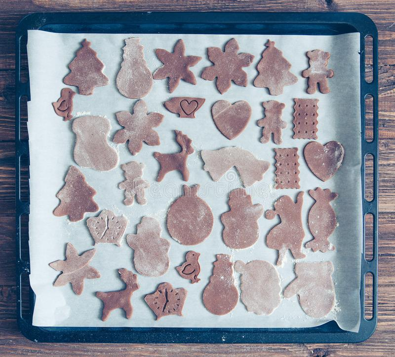 Gingerbread Cookie. New Year and Christmas figures from a chocolate dough, prepared for baking in the oven. Cookies in the form of royalty free stock image